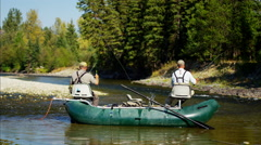 Males fly fishing from rib boat freshwater River Canada BC - stock footage