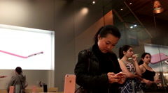 Women buying new iphone inside Apple store Stock Footage