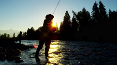 Sunrise silhouette of freshwater river fishing male and female casting Stock Footage