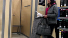 Woman trying new clothes in dressing room inside Walmart store - stock footage