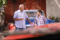 Grandfather Telling History Of Vintage Car To Grandson - stock photo