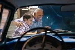Boy With Grandpa Looking Car Engine Of Senior Man - stock photo