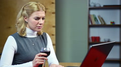 Surprised woman reading latest news on the internet, drinking red wine Stock Footage
