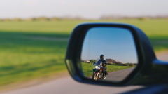 The car ahead of the motorcycle, the view through the rear-view mirror Stock Footage