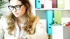 Irritated businesswoman sitting in office and being bothered, steadycam shot - stock footage