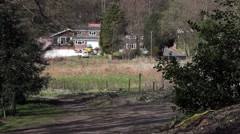 Distant shot of car passing house near forest pool Stock Footage