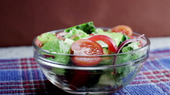 Salad with fresh cucumbers, tomatoes, onions and lettuce Stock Footage