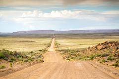 Long, straight dirt road - stock photo