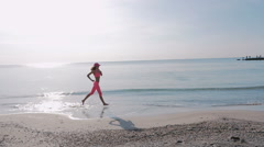 Young woman running at sea coast at sunrise with spray, slow motion - stock footage