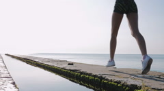 Young woman running on sea pier at sunrise, silhouette, slow mo Stock Footage