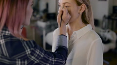Girl stylist working in a beauty studio. Make-up for a beautiful blonde. Working - stock footage