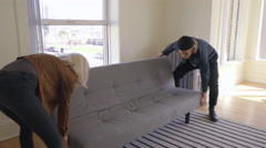 Couple Move A Couch Into Their First Place Together, They Set It Down, Adjust It Stock Footage