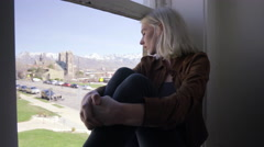 Young Woman Sits In Window And Looks Out At City And Mountain View Stock Footage