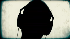 Silhouetted male head with headphones, enjoying music Stock Footage
