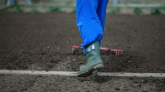 Raking the soil along the wooden board in the garden Stock Footage