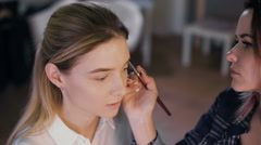 Make-up artist work on her friend. Real people - stock footage