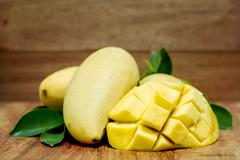 Mango on a dark wood background. tinting. Stock Photos