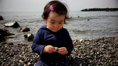 Stock Video Footage of Baby self employed on the stones beach in spring.