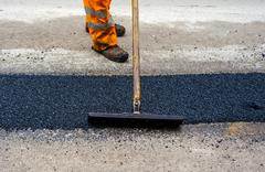 Construction Worker during Asphalting Road Works. - stock photo