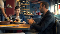 Young couple getting food from waiter in cafe  Stock Footage