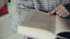 Close up shot of woman's hand reading a book indoors. Stock Footage