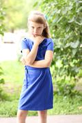Stock Photo of Little girl  blue dress bright sunny summer day park among green bushes, looking