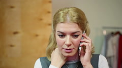 Person hearing bad news. Blond woman talking on the smartphone and feeling sad Stock Footage
