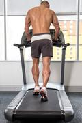Young Man On Treadmill Back View - stock photo