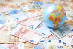 Earth globe over the pile of money Kuvituskuvat