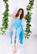 Beautiful young leggy redhaired woman in a long blue dress on a swing, wooden Stock Photos