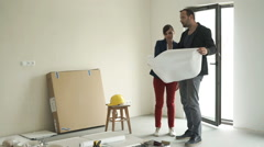 Sad, unhappy couple talking and checking blueprints at their new home Stock Footage