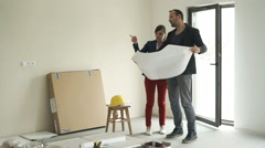 Couple talking and checking blueprints at their new home Stock Footage