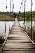 pendant bridge over river - stock photo