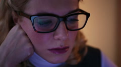 Tired woman wearing glasses, browsing internet pages on laptop at night Stock Footage