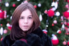 Beautiful brown-eyed brunette girl  winter  black coat posing  background trees Stock Photos