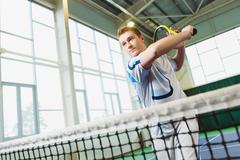 Low angle view of determined young man playing tennis indoor - stock photo