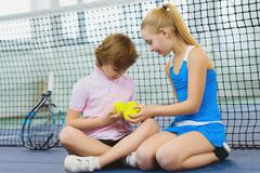 Children having fun and resting on the tennis court Stock Photos