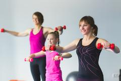 Two young woman and little girl doing gymnastic exercises Stock Photos