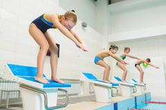 Children ready to jump into sport swimming pool. Sporty kids Kuvituskuvat