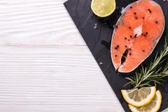 Raw salmon fillet and ingredients for cooking ,wooden background - stock photo