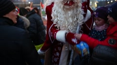 Ded Moroz handing out boxes of chocolates to children on playground Stock Footage