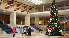 Christmas tree and people walk past in hall of State Kremlin Palace Stock Footage