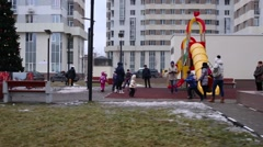 Children and adults on playground among high-rise buildings Stock Footage