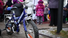 Childrens bicycle in front of children playing with animator Stock Footage
