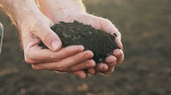 Farmer handful of fertile soil standing in cultivated field Stock Footage