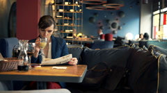 Young woman reading magazine and drinking cocktail in cafe Stock Footage