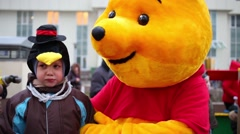 Sad boy with animator dressed as Winnie the Pooh Stock Footage