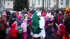Children with Snowman and Christmas tree in circle holding hands Stock Footage