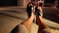Feet in slippers men swinging in hammock in night. - stock footage