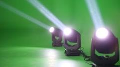 Three spotlights shining light rays in green studio on shooting video Stock Footage